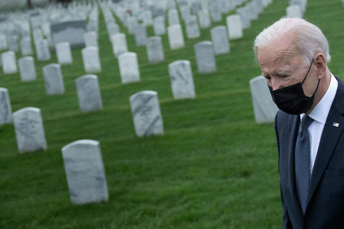"""US President Joe Biden walks through Arlington National cemetary to honor fallen veterans of the Afghan conflict in Arlington, Virginia, on April 14, 2021. - President Joe Biden announced it's """"time to end"""" America's longest war with the unconditional withdrawal of troops from Afghanistan, where they have spent two decades in a bloody, largely fruitless battle against the Taliban. (Photo by Brendan Smialowski / AFP) (Photo by BRENDAN SMIALOWSKI/AFP via Getty Images)"""