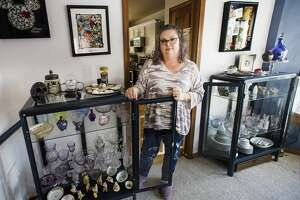 Kim Padavana poses for a portrait with her collection of purple manganese glass Thursday, Feb. 11, 2021 at her home in Midland. (Katy Kildee/kkildee@mdn.net)