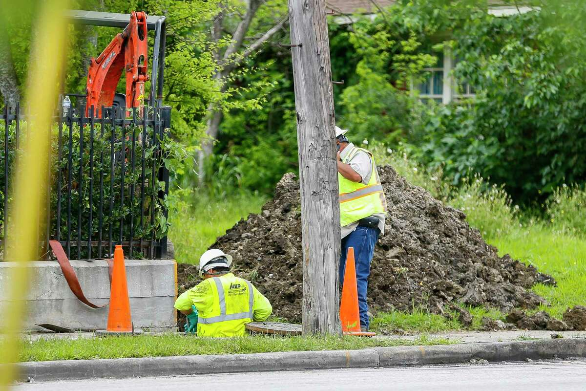 Contractors work to make repairs on a city sewer line that runs behind homes on Jefferson Street at Telephone Road, Thursday, April 2, 2020, in Houston.