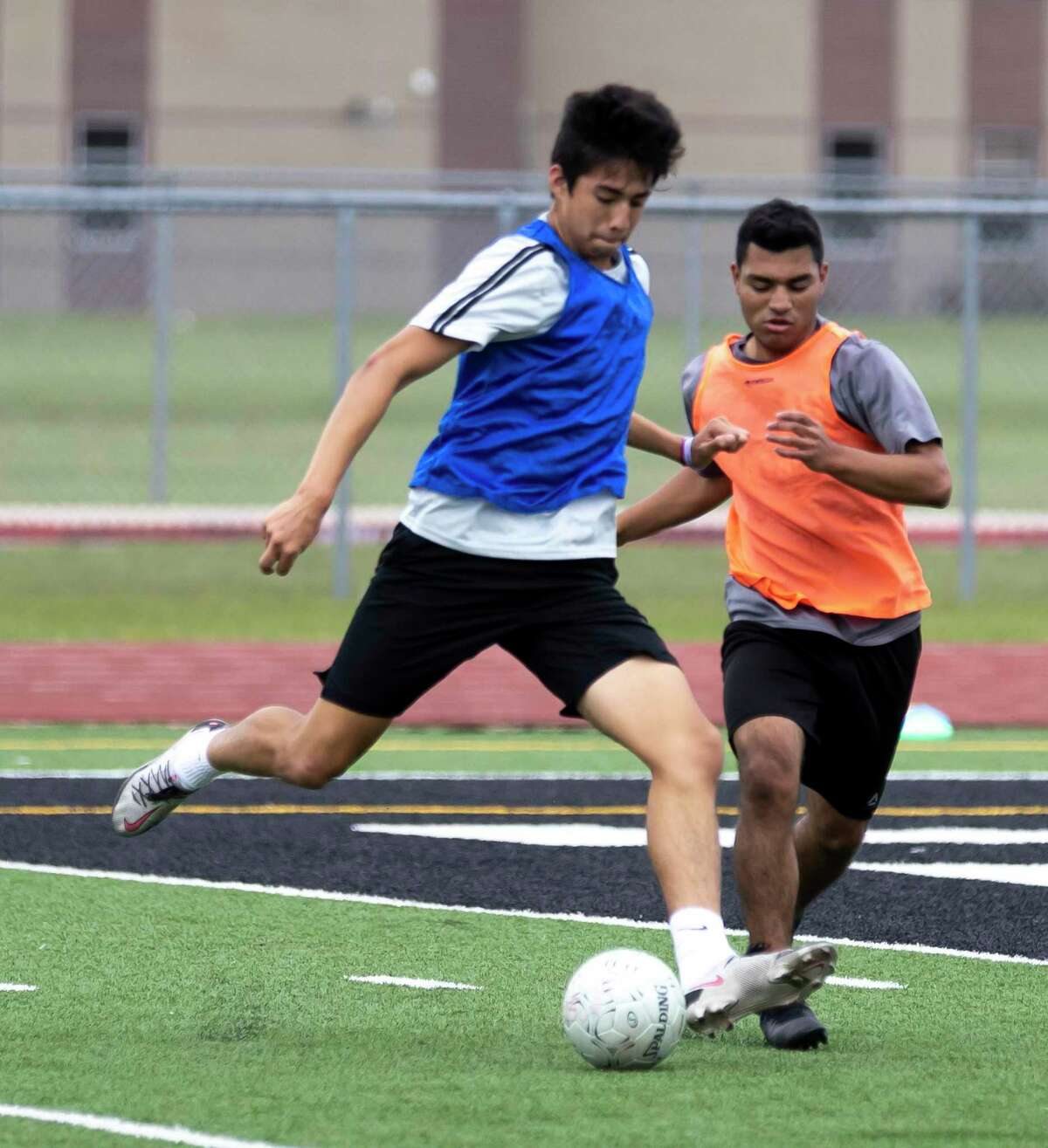 Jesus Cervantes of Kingwood Park, senior, left, kicks the ball while under pressure during practice at Panthers Stadium in Kingwood Park High School, Thursday, April 15, 2021, in Kingwood. Kingwood Park will faceoff Wakeland High School, Saturday, April 17, during the 2021 Boys Soccer State Championship - UIL 5A Boys Soccer Championship in Georgetown.
