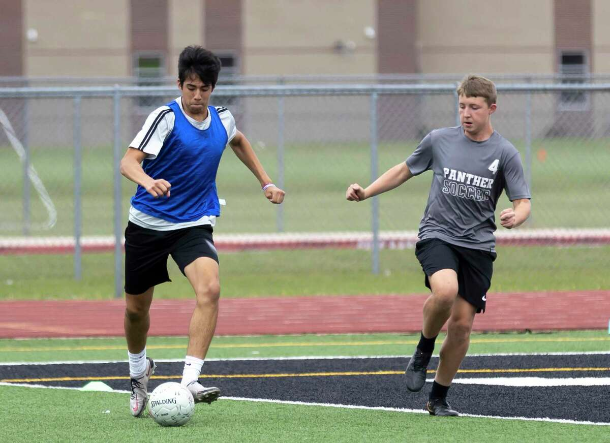 Jesus Cervantes of Kingwood Park, left, drives the ball while under pressure from a teammate during practice at Panthers Stadium in Kingwood Park High School, Thursday, April 15, 2021, in Kingwood. Kingwood Park will faceoff Wakeland High School, Saturday, April 17, during the 2021 Boys Soccer State Championship - UIL 5A Boys Soccer Championship in Georgetown.