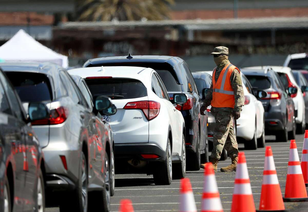 An officer with the Air National Guard wait in front of a vehicle as cars wait in line in observation lanes at the Oakland Coliseum vaccination site on Thursday, March 25, 2021, in Oakland, Calif. The Coliseum vaccination site is only scheduled to be open for eight weeks, which means it will close in three weeks unless a deal is reached with local officials.