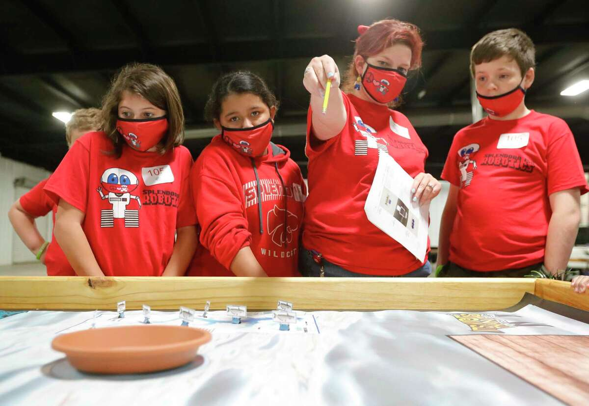 Splendora teacher Aex Kabi instructs Klinton Cool and the rest of her team during the ag robotics competition at the Montgomery County Fair & Rodeo, Friday, April 16, 2021, in Conroe. This competition offered students from Montgomery County with an interest in STEM related fields the opportunity to competed against their peers in an agricultural focused course designed to challenge students to use their robot to complete various tasks for points.