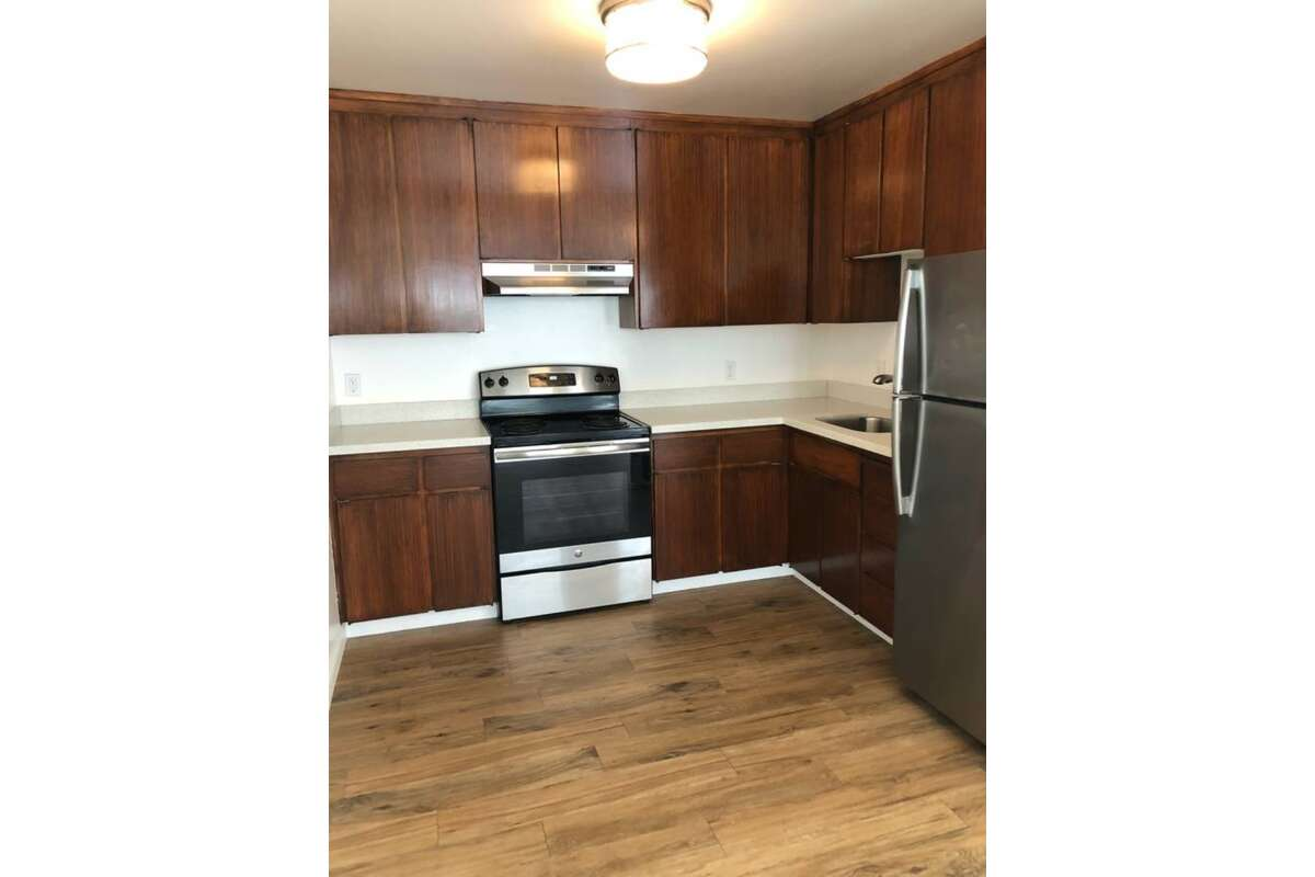 The listing describes the kitchen as updated with quartz countertops. It doesn't look like there is a dishwasher, but it may be out of view. It also says it has LED light fixtures throughout the entire unit. There is an open floor plan and the kitchen flows into the living room.