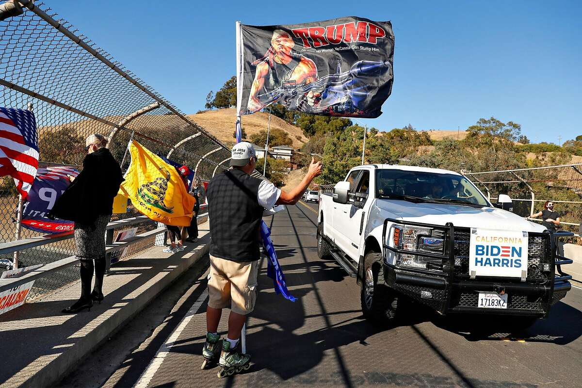 A supporter of US President Donald Trump, who didn't want to be identified, waves as a President-elect Joe Biden supporter drives past on El Curtola Boulevard overpass over Highway 24 in Lafayette, Calif., on Saturday, November 7, 2020.