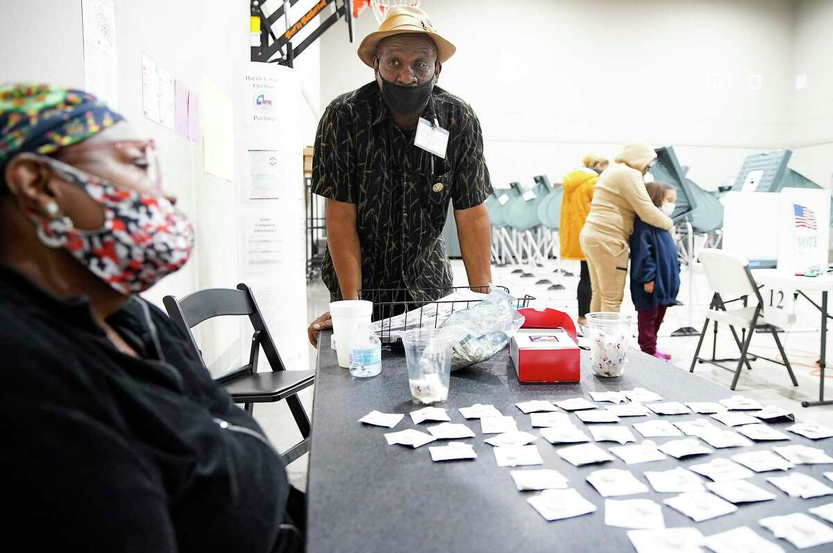 Election judge Herman Williams chats with a poll worker at Victory Houston polling station in Houston on Oct. 30, 2020. The location was one of the Harris County's 24-hour locations.