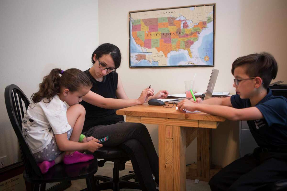 Nurse practitioner Janette Adams works with her children, Maddie and Henry, helps people find COVID-19 vaccine appointments from their home office in Spring.