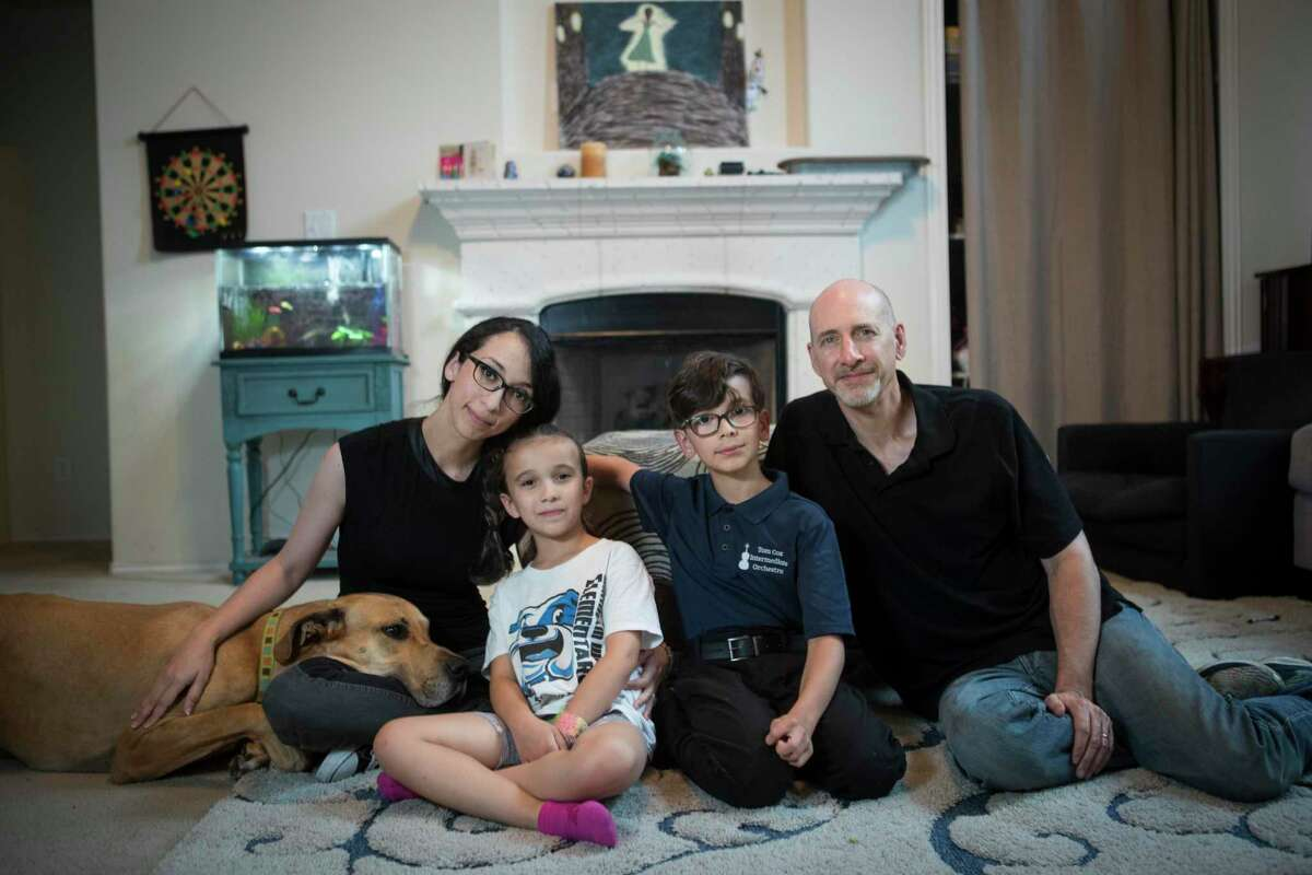 Nurse practitioner Janette Adams poses for a portrait with her children, Maddie and Henry, her husband Rick and their dog, Charlie, in their home in Spring. She has helped more than 500 friends, relatives and strangers find vaccination appointments.