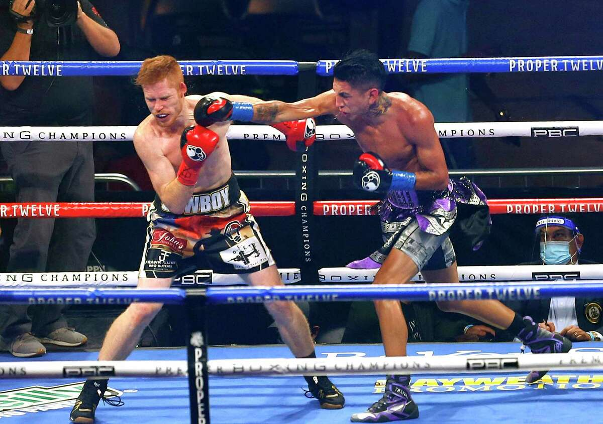 Mario Barrios, right, connects with a right against Ryan Karl during their WBA junior middleweight boxing bout Saturday, Oct. 31, 2020, in San Antonio. (AP Photo/Ronald Cortes)