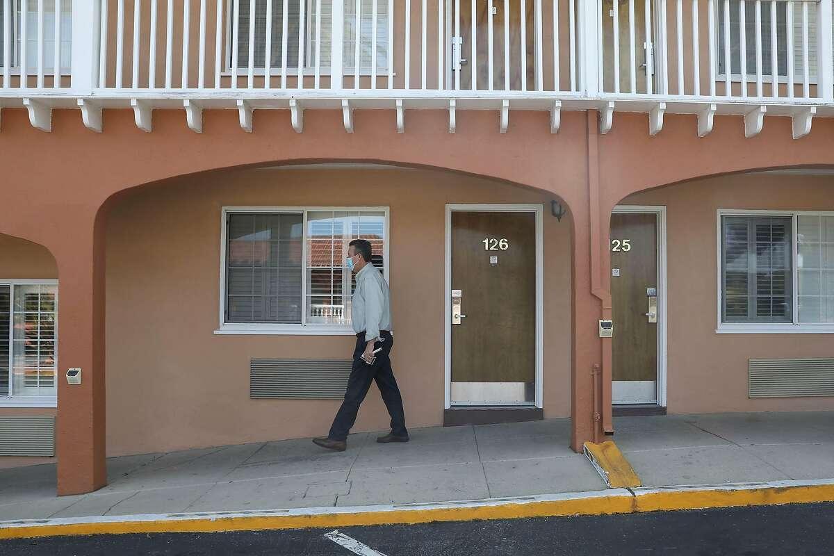 Art Schwass, general manager El Rancho Inn, walks past rooms at the El Rancho Inn in Millbrae.