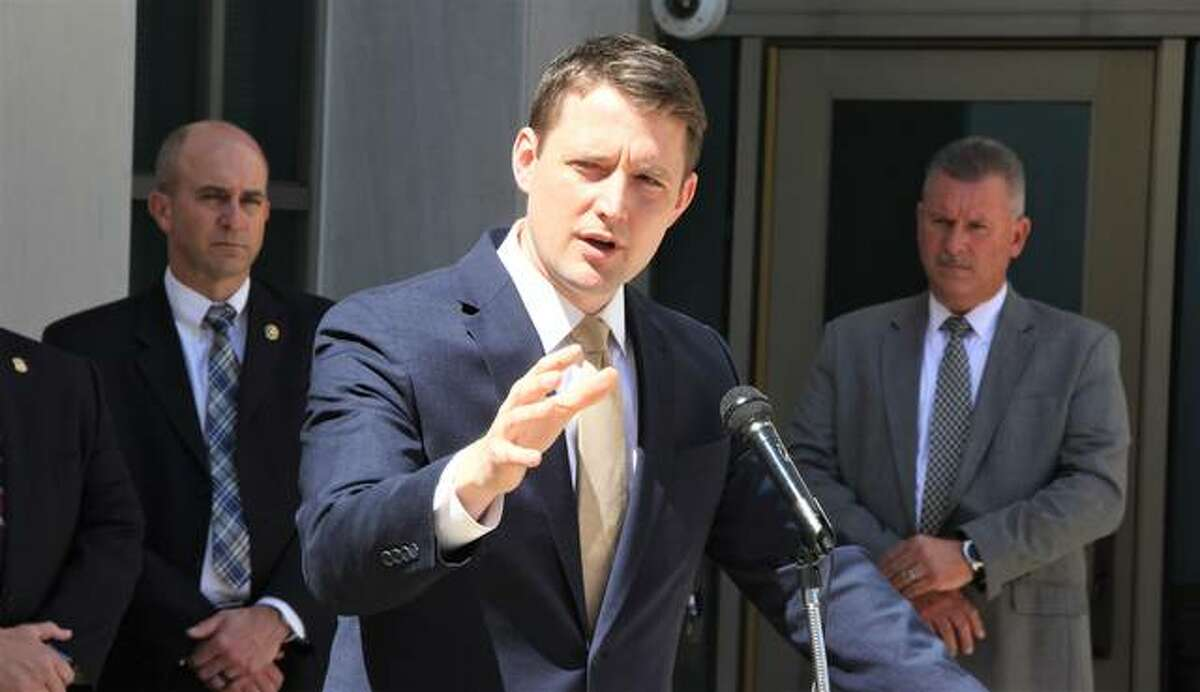 """Madison County State's Attorney Thomas Haine, flanked by Brad Maxwell, U.S. Marshal for the Southern District of Illinois, left, and Madison County Chief Deputy Sheriff Maj. Jeff Connor, while talking about the results of a meeting among Madison County, state and federal law enforcement officials concerning """"cross-river"""" crime, April 9."""