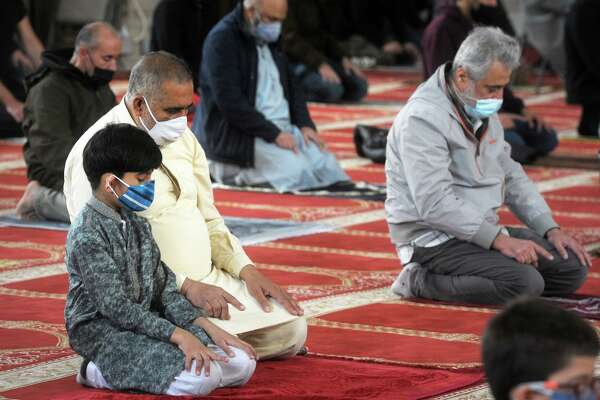 Khadim Khan and his son Mihad join other worshipers as they gather to pray on the first Friday of the Islamic holy month of Ramadan, at the Bridgeport Islamic Community Center, in Bridgeport, Conn. April 16, 2021.