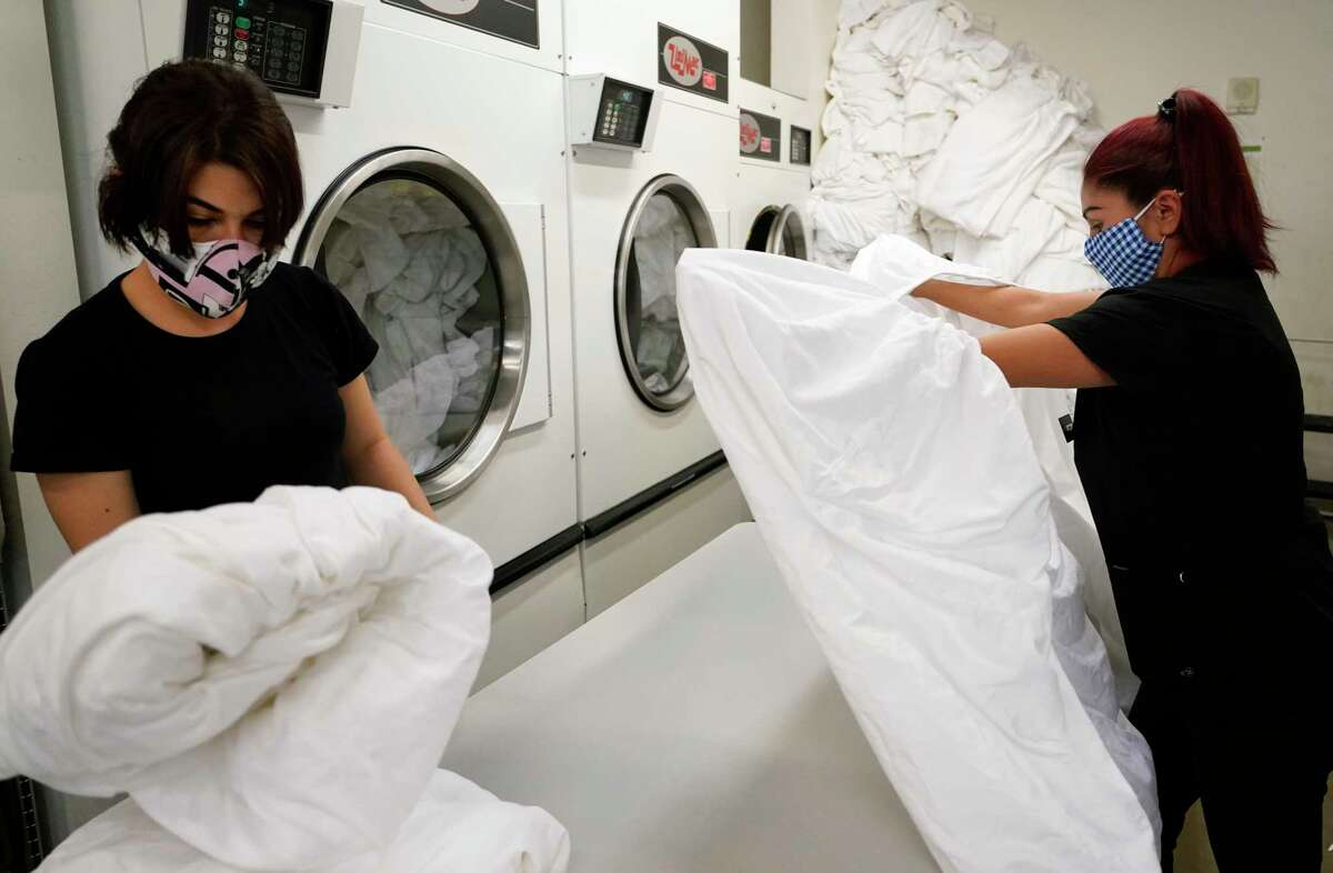 Housekeepers Veka Rivas, left, and Rosie Bahena, right, fold sheets at The Moran CityCentre, 800 Sorella Ct., Friday, April 16, 2021 in Houston.