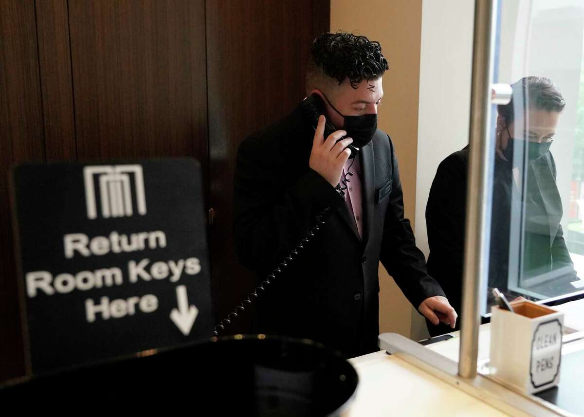Danny Ruiz, front office manager, left, and Tabitha Edgington, front desk agent, work at the front desk at The Moran CityCentre, 800 Sorella Ct., Friday, April 16, 2021 in Houston.