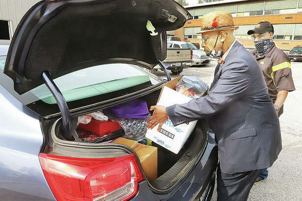 """Gary Woods, left, and Joe Elliott, load food boxes into the trunk of a car Friday morning behind Horace Mann School in Alton. The men were helping with the first ever """"pop trunk, drive through"""" food distribution by the 100 Black Men of Alton with help of sponsors."""