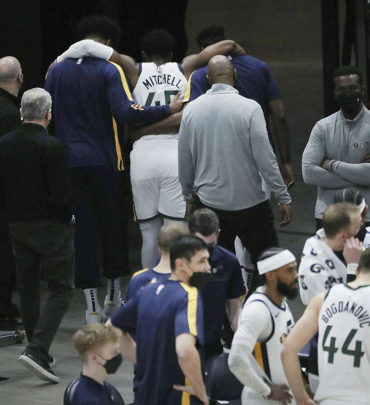 Jazz guard Donovan Mitchell is helped off the court by teammates after suffering an injury in the second half. He was to undergo an MRI exam.