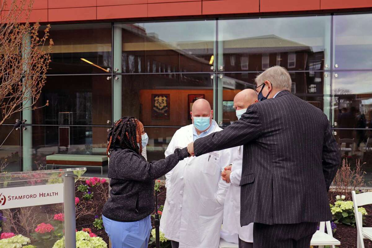 Trisha Lors, Dr. Michael Bernstein, Dr. Michael Perry and Mayor David Martin fist bump during the dedication of the COVID-19 memorial garden at Stamford Health on Friday, April 16, 2021.