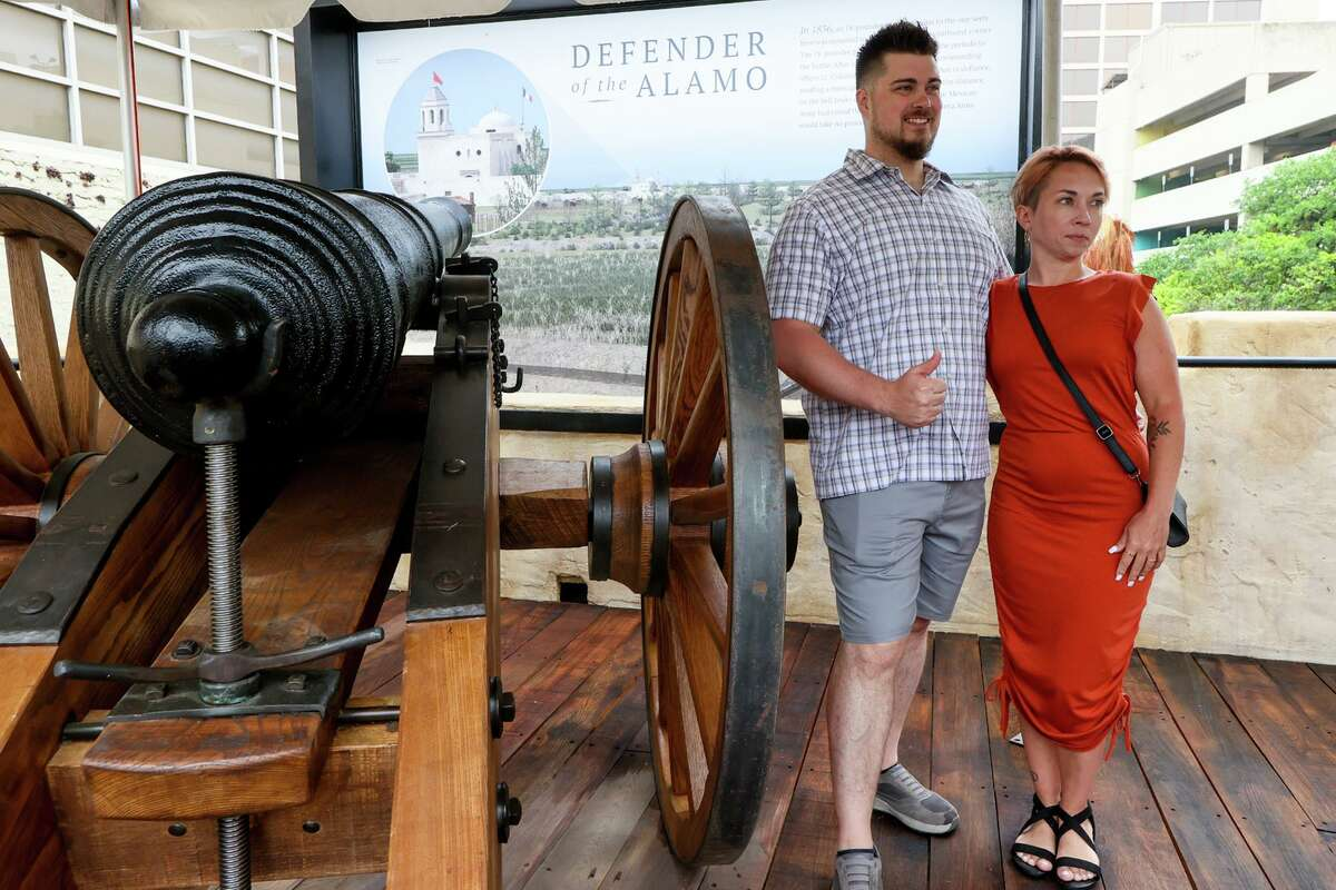 Andrew Unger and Jeanette Patwell, visiting from Chaska, MN, pose for a photo beside the replica 18-Pound cannon as state and local officials gathered for the unveiling of a new outdoor
