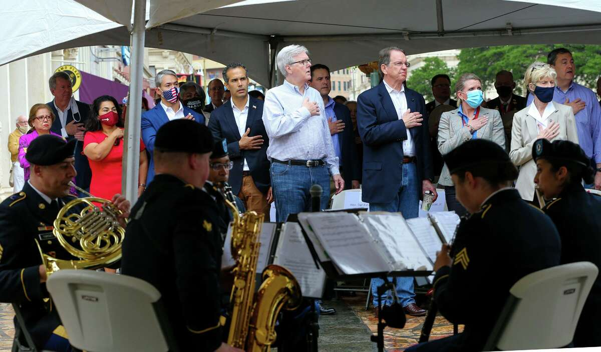 Texas Lt. Governor Dan Patrick, center, stands at attention with other state and local offic1als as the national anthem is played by members of the Ft. Sam Houston Army Band at the unveiling of a new outdoor
