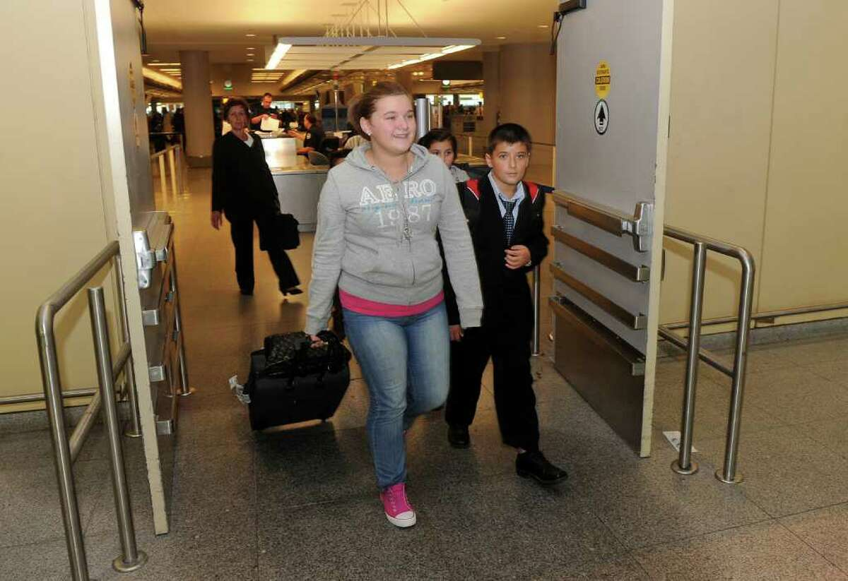 Dorontina Emini, 13, and her brother Dorart, 12, emerge from customs at JFK International Airport in New York City, with the rest of their family on Friday September 10, 2010. The Emini's have returned from Serbia after being there since June.