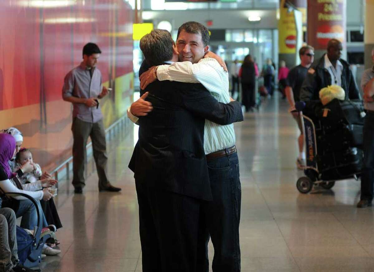 Family friend Ilber Ramadani, of Naugatuck, reacts with smiles as he embraces Skender Emini, left, after he arrived with his family at JFK International Airport in New York City on Friday September 10, 2010. The Emini's have returned from Serbia after being there since June.