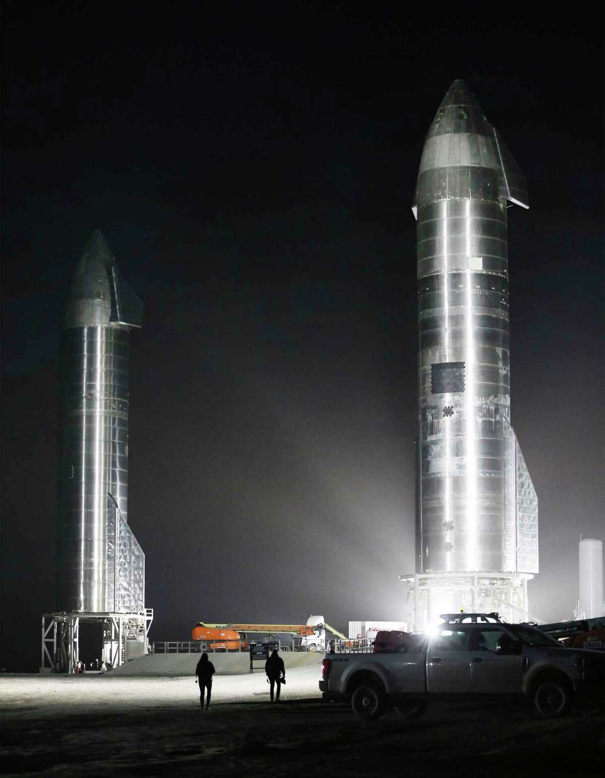 SpaceX personnel walk toward the SpaceX SN9 and SN10 rockets on Sunday, Jan. 31, 2021 at Boca Chica Village, Texas.
