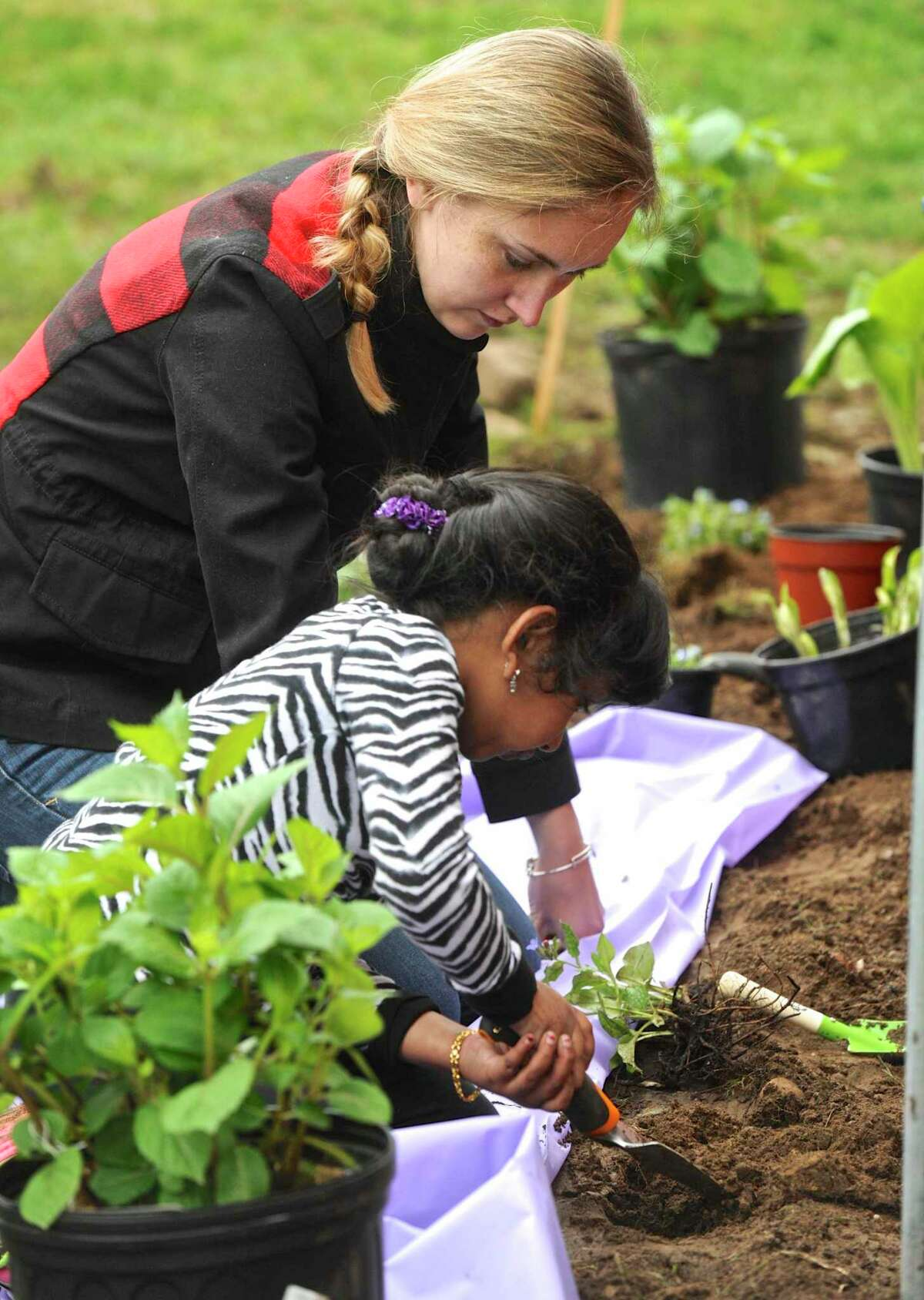 Emily Prescott, with the Brookfield Conservation Commission, helps Jasiel Merlin, 6, of New Milford, plant flowers during the commissions Earth Day celebration at Gurski Homestead. Saturday, April 22, 2017, in Brookfield, Conn.