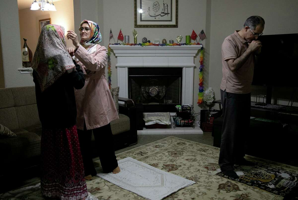Sumeyra Tek, right, wraps a scarf for her daughter, Hafsa, 12, to wear for their prayer with her husband and Hafsa's father, Suleyman Tek, after the virtual gathering with the Raindrop Foundation for the Ramadan fast-breaking dinner at their home in San Antonio on April 15, 2021.