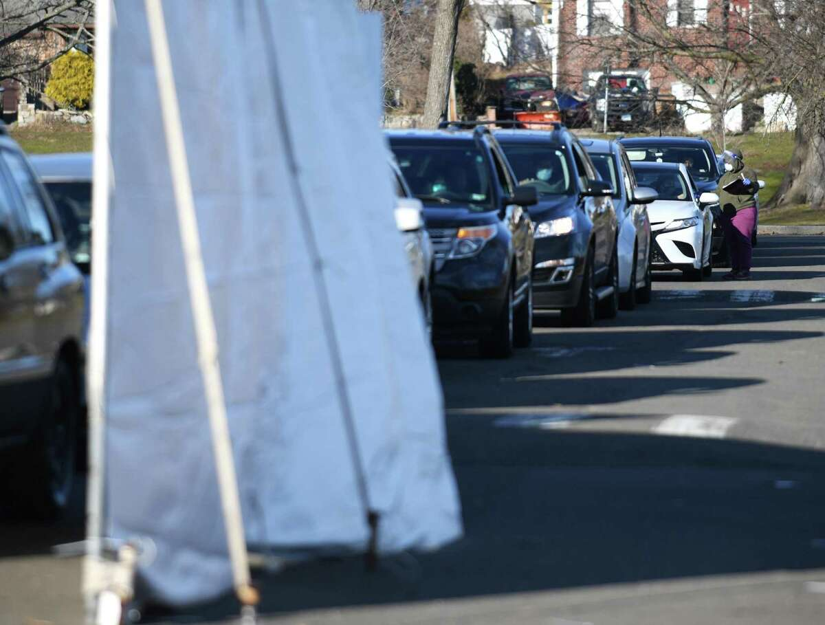 A line of cars wait at the drive-thru COVID-19 test site at Cove Island Park in Stamford, Conn. Sunday, Jan. 10, 2021. Operated by Community Health Center, the Cove Island COVID-19 testing is free of charge and open every day from 8:30 a.m. to 4 p.m.