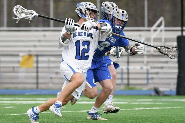 Darien's Jamison Moore (12) takes a shot while Glastonbury's Liam Doyle (9) defends Friday's game.