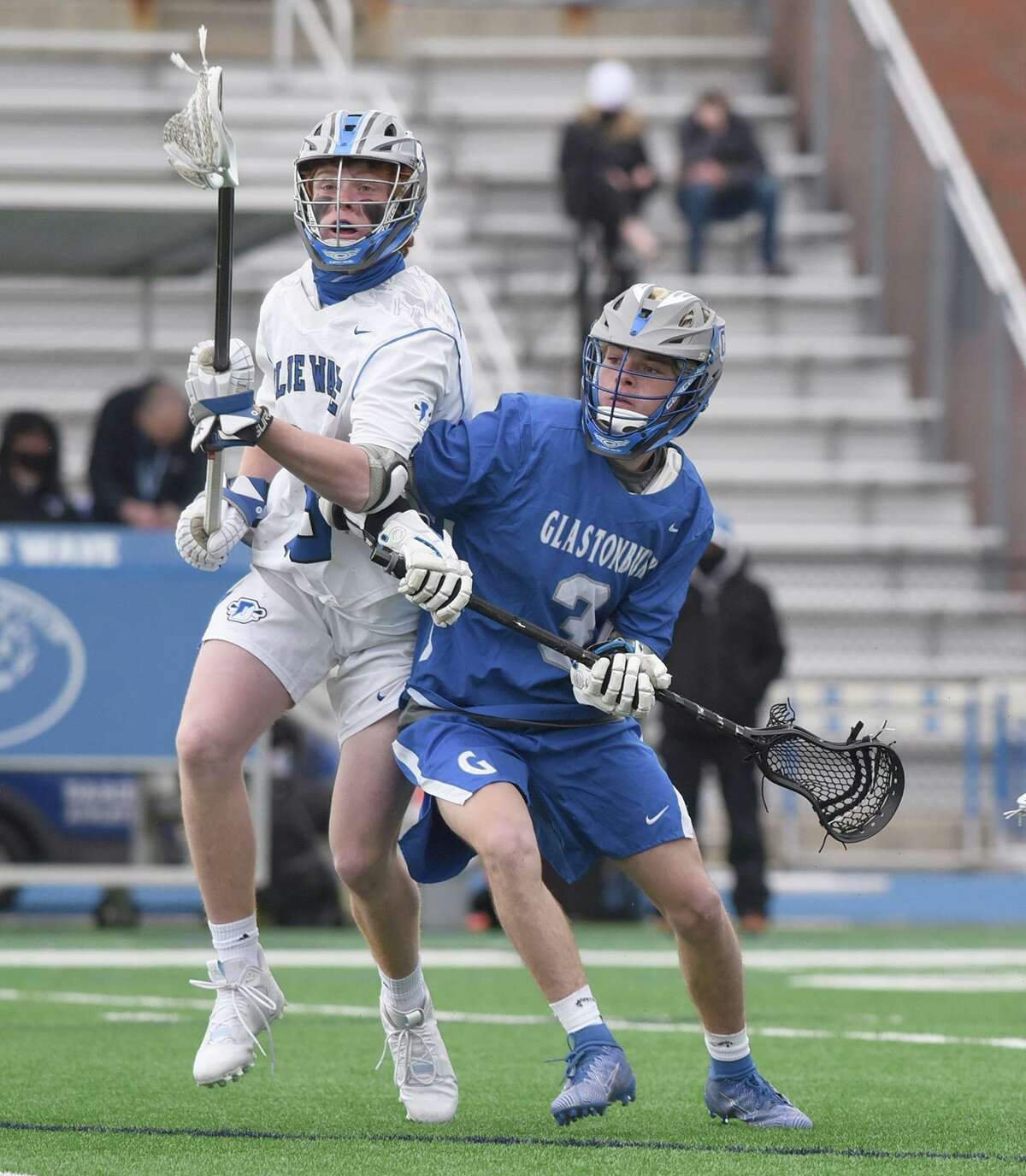 Darien's Mac McGahren (23) and Glastonbury's Capers Shaw (3) battle for the ball during a boys lacrosse game at Darien High School on Friday, April 16, 2021.