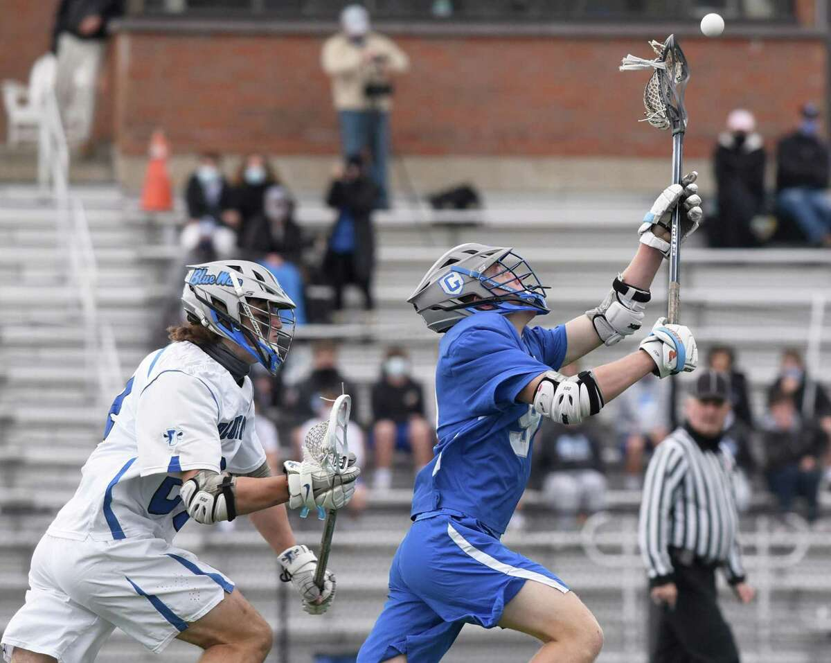 Glastonbury's Liam Doyle (9) reaches for the ball while Darien's Christian Alliegro (24) pursues during a boys lacrosse game at Darien High School on Friday, April 16, 2021.
