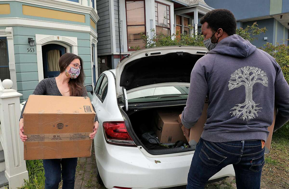 Ernest Brown and Alison Grady pack their belongings into their car in Oakland on March 24, 2021, before their move to Atlanta. The couple decided to leave the Bay Area to buy a home in a place they could afford and start a family.