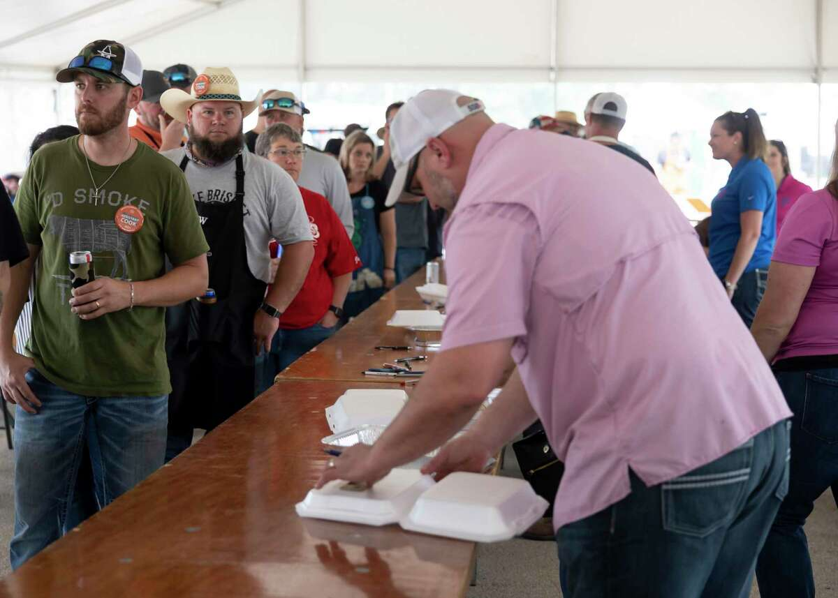 Participants of the Midnight Love Street BBQ Cookoff line up to collect their competition plates at the Montgomery County Fair & Rodeo, Friday, April 16, 2021, in Conroe. An estimated 110 teams competed in this year's cookoff.