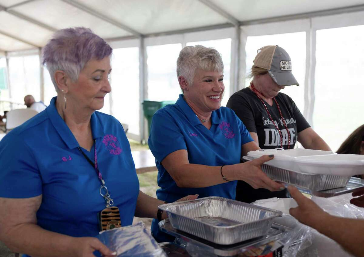 From left, B.J. McGuirde, Lara Johnson and Melissa Wickham hand out plates Friday during the Midnight Love Street BBQ Cookoff at the Montgomery County Fair & Rodeo in Conroe.