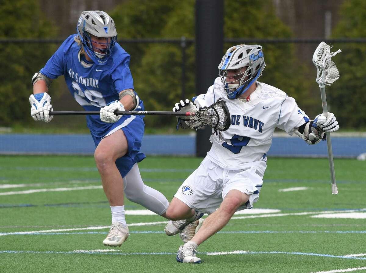 Darien's Matt Stein (9) battles Glastonbury's Lance Dominick (29) during a boys lacrosse game at Darien High School on Friday, April 16, 2021.