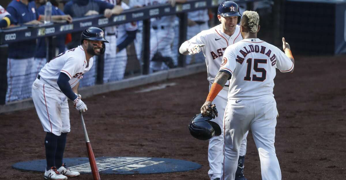 Houston Astros Jose Altuve, left, and Alex Bregman (2) greet Houston Astros Martin Maldonado (15) at the dugout as they celebrate after he scored on a 2-run double by Houston Astros Michael Brantley (23) during the third inning of Game 5 against the Tampa Bay Rays in the American League Championship Series at Petco Park Thursday, Oct. 15, 2020, in San Diego.