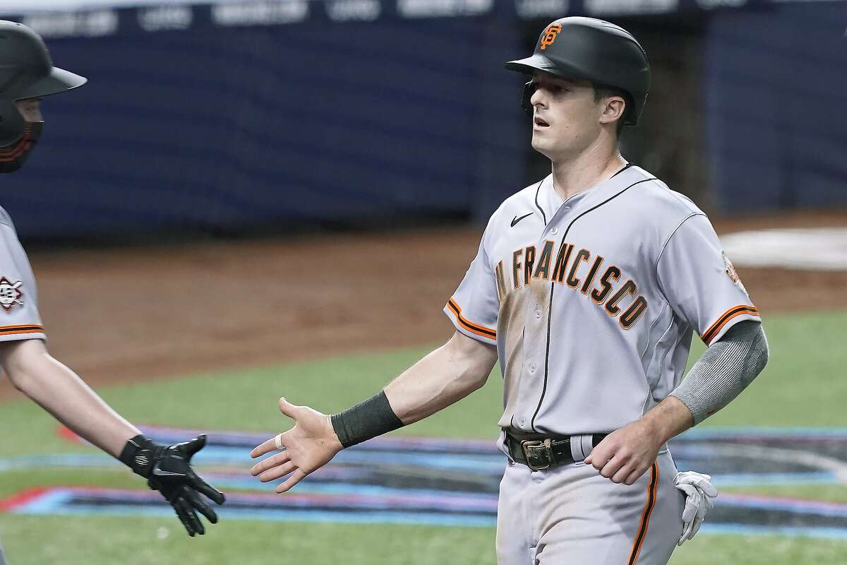 San Francisco Giants' Mike Yastrzemski (5) scores a run during the fourth inning of a baseball game against the Miami Marlins, Friday, April 16, 2021, in Miami. (AP Photo/Marta Lavandier)