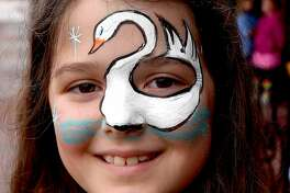 Poppy Hebert sports a swan face painting during the Neches River Festival Street Party on Crockett Street Friday. The annual downtown parade was canceled due to the weather, but a band played inside The Gig, there were children's activities outdoors, beverages, food and more to keep the spirit of the night festive despite the rain. Photo made Friday, April 16, 2021 Kim Brent/The Enterprise
