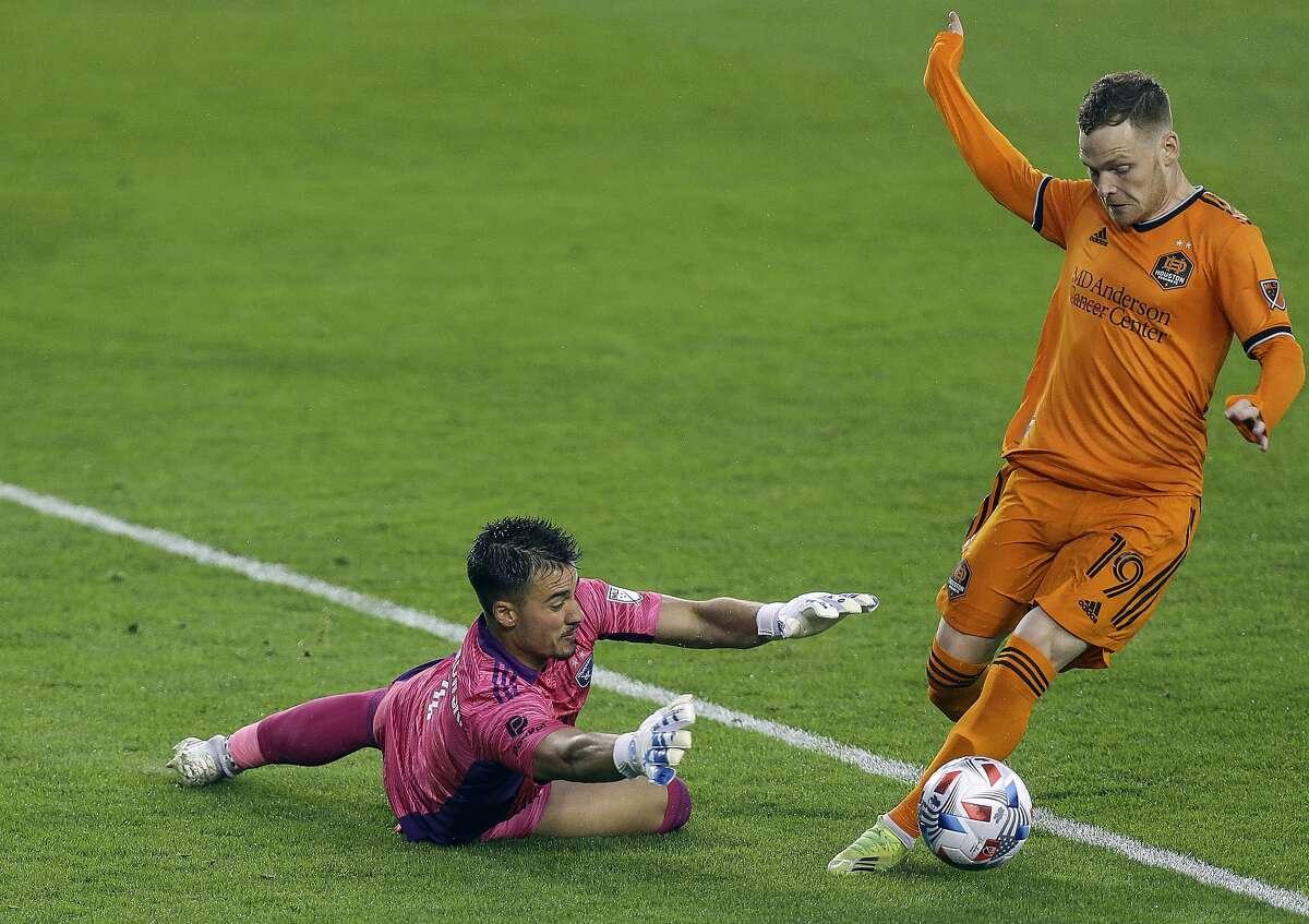 Earthquakes goalkeeper JT Marcinkowski makes a save against Houston's Tyler Pasher.