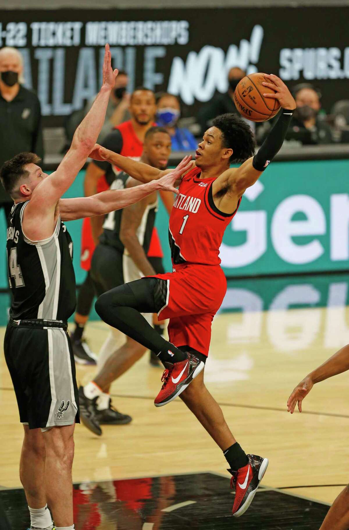 SAN ANTONIO, TX - APRIl 16: Arnfernee Simmons #1 of the Portland Trailblazers drives over Drew Eubanks #14 of the San Antonio Spurs in the second half at AT&T Center on April 16, 2021 in San Antonio, Texas. NOTE TO USER: User expressly acknowledges and agrees that , by downloading and or using this photograph, User is consenting to the terms and conditions of the Getty Images License Agreement. (Photo by Ronald Cortes/Getty Images)