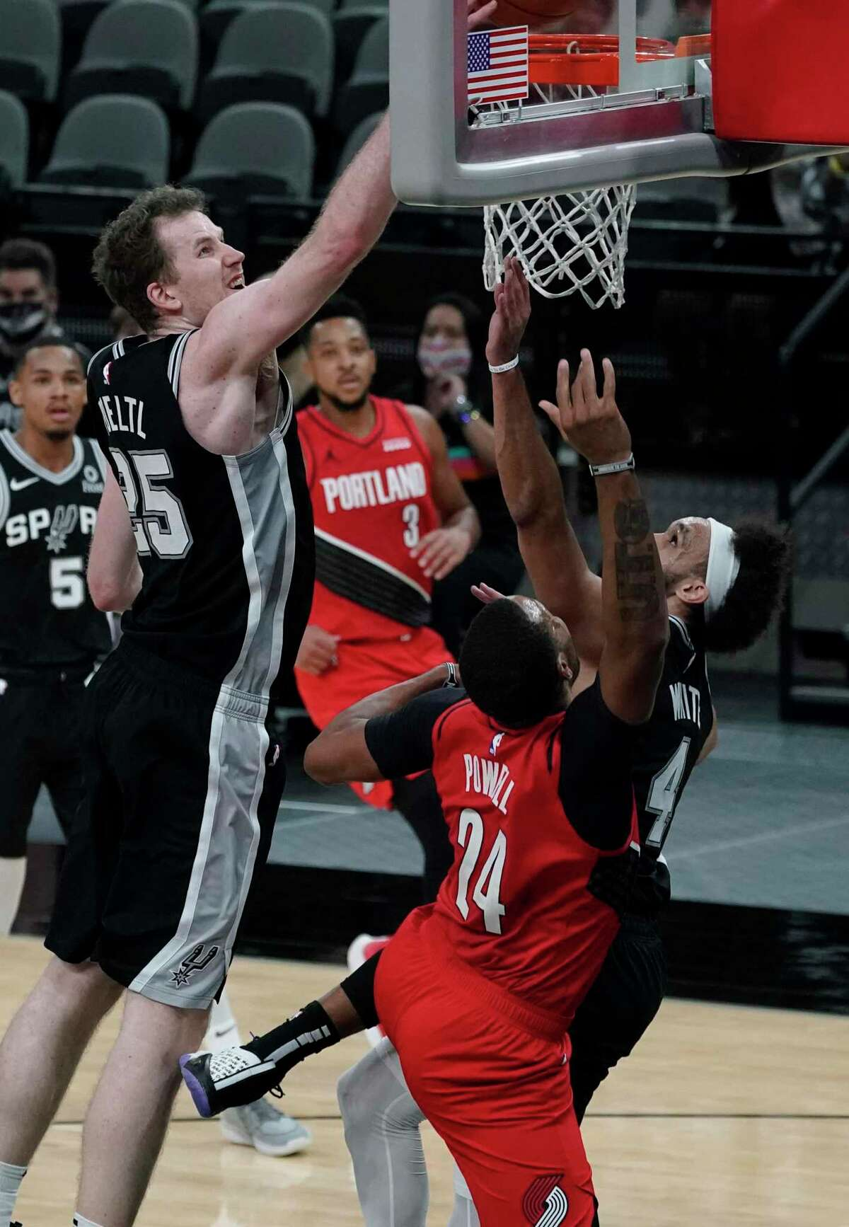 Portland Trail Blazers forward Norman Powell (24) scores the winning points past San Antonio Spurs center Jakob Poeltl (25) during the second half of an NBA basketball game in San Antonio, Friday, April 16, 2021. (AP Photo/Eric Gay)