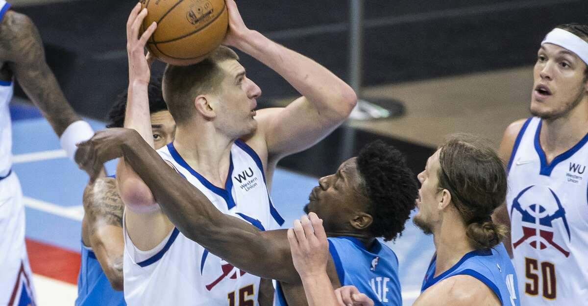 Denver Nuggets center Nikola Jokic (15) works over three Rockets defenders during the third quarter of an NBA game between the Houston Rockets and Denver Nuggets on Friday, April 16, 2021, at Toyota Center in Houston.