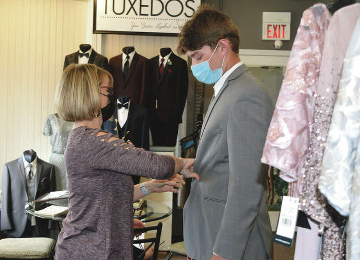 Melinda Norton of Girls in White Satin Bridal and Formal Wear measures a tuxedo Friday for Jacksonville High School student Will Rohlk.