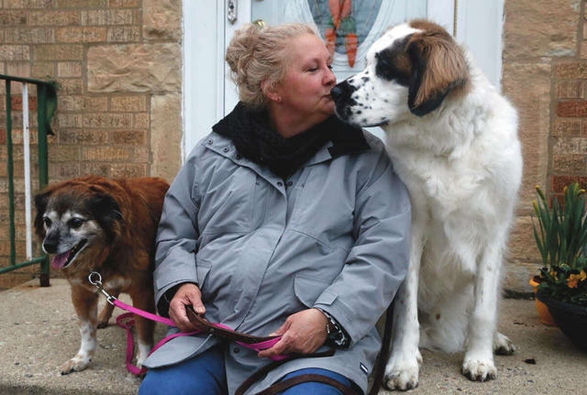 """Janine Blezien sits with her dogs, Kasey and Gordy. Blezien, who is single, said talking with retiree Dianne Green, through the Rush University Medical Center's """"friendly caller"""" program, also helped her feel less isolated last year. """"We just clicked,"""" she said."""