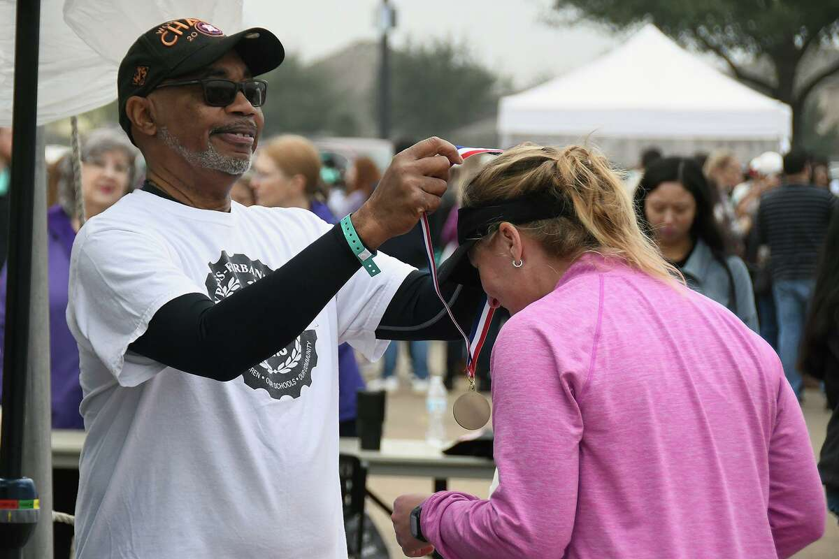 """In this photo from before the pandemic, a Fun Run participant is awarded a medal. This year, the Cy-Fair ISD Superintendent's Fun Run will be virtual, encouraging participants to """"run together from wherever."""""""