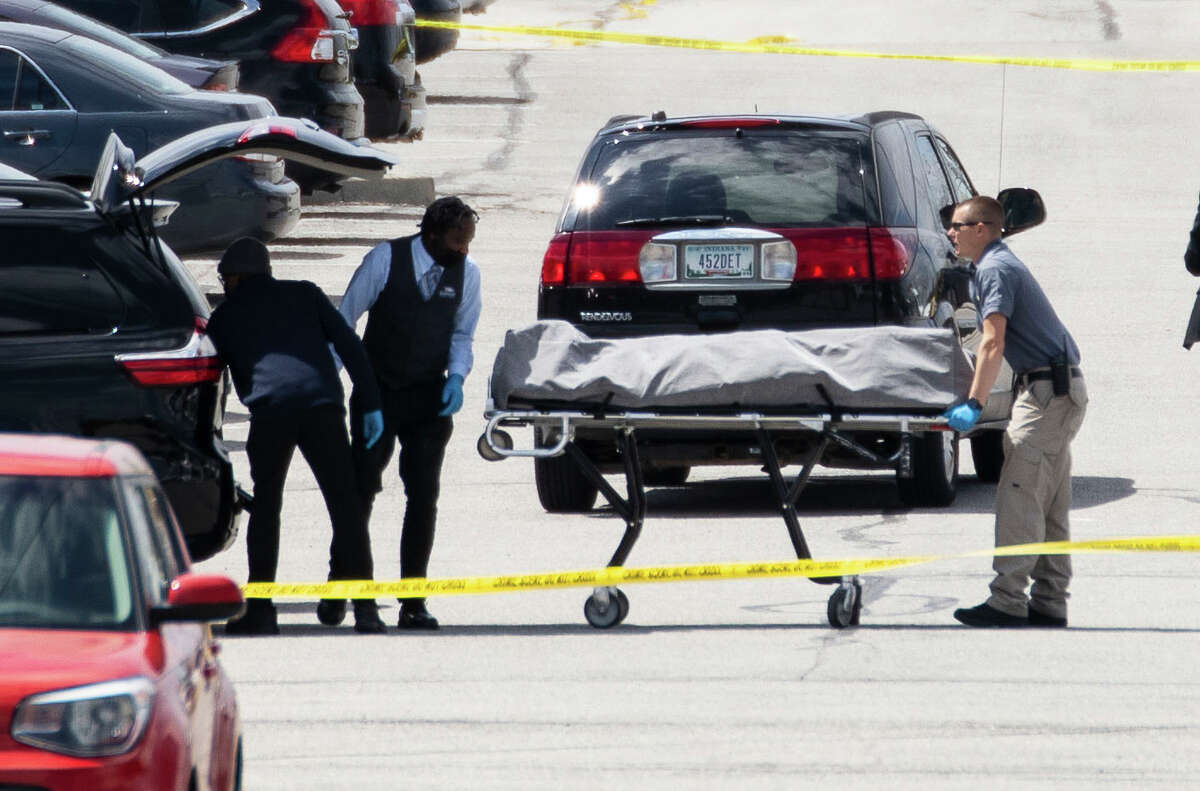 Bodies are carried away on Friday from the scene of a mass shooting that took place at a FedEx facility in Indianapolis.
