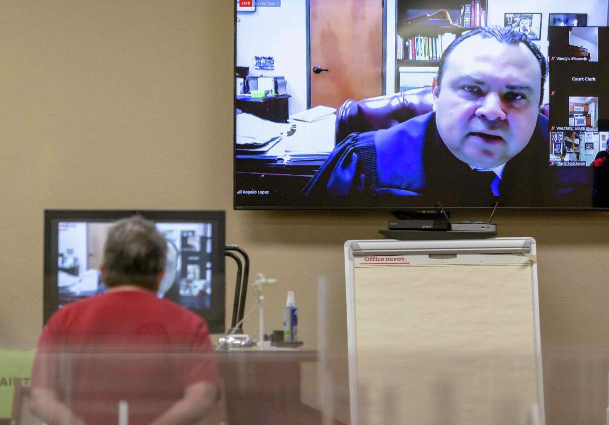 Justice of the Peace Precinct 4 Judge Rogelio Lopez appears on screen while a landlord listens Wednesdayduring a hybrid online/in-person eviction hearing.