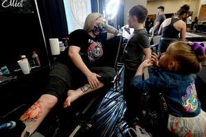 Cassie Terrell talks with her children Ethan Terrell and Alex Elliott as she gets a piece worked on by her partner Jason Elliott of College Station on the opening day of this weekend's Ink Masters Tattoo Show at the MCM Elegante in Beaumont. Renowned tattoo artists from the region will be scheduling appointments and doing walk-up tattoos, and other vendors are on-site, as well. The event continues Saturday 11 a.m. - 11 p.m., and Sunday 11 a.m. - 9 p.m. Photo made Friday, April 16, 2021 Kim Brent/The Enterprise
