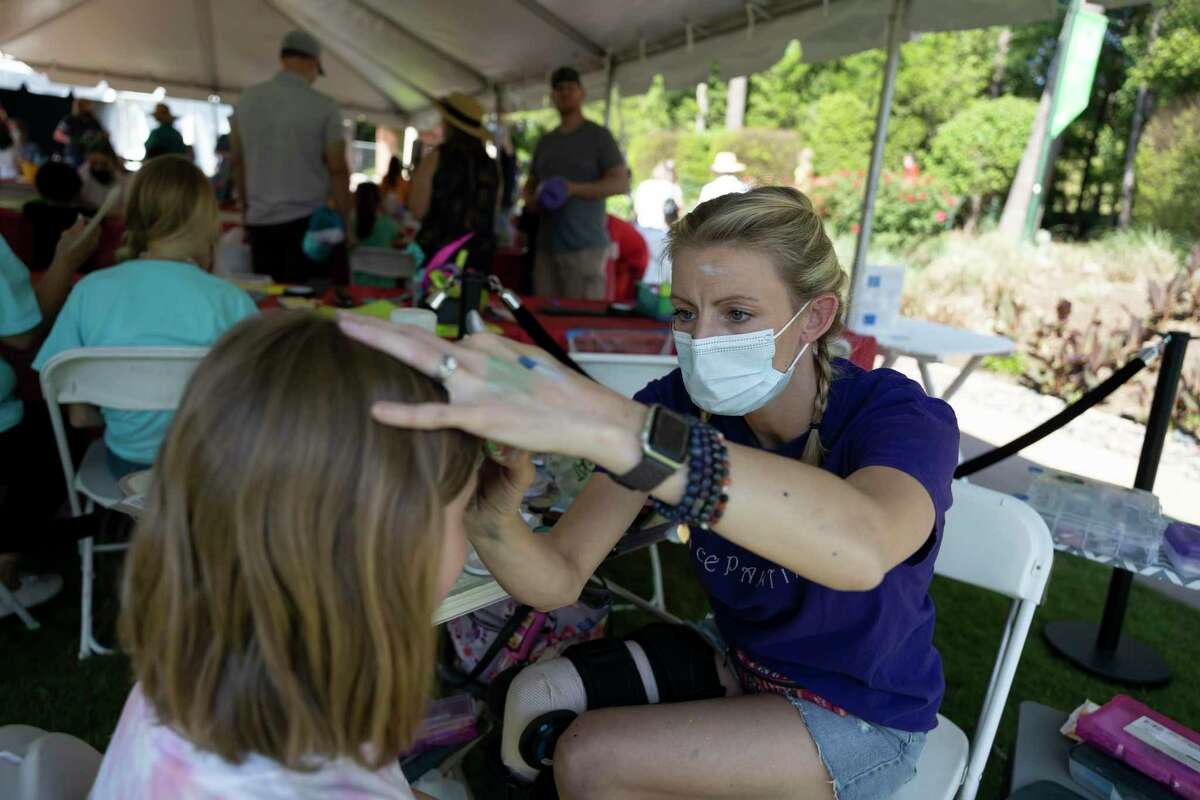 Kate Welter, owner of Kate's Face Painting, paints an animal on Rachel Allan's face during The Woodlands Waterway Arts Festival, Saturday, April 10, 2021, in The Woodlands. The festival was held virtually last year due to the COVID-19 pandemic but was held in-person this year.